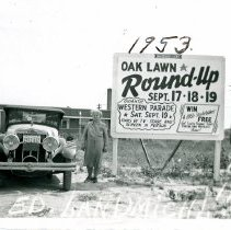 Image of 1953 Round Up Advertising Sign - This is a photograph featuring Mrs. Landmichl standing next to a 1925 Franklin Sport Roadster Model 11-A-AT on the southeast corner of 95th Street and Southwest Highway next to a sign advertising the 1953 Oak Lawn Round-Up. The sign was made by Van Bruggen Signs located at 7101 W. 127th Street in Palos Park. The car was owned by her son, Edward Landmichl, Jr. The building in the background in believed to be the medical office of Dr. Ruben Liberstein. The picture is marked with the photographer's name in handwriting seen across the bottom of the picture in white and the year above the sign in black.