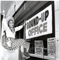 Image of Round-Up Days, 1958 - This is a photograph featuring Beth Cole (7), outfitted in cowgirl gear complete with holsters and six-shooter cap guns, in front of the Annual Round-Up Days event headquarters. Posters in the window announce the dates of Round-Up Days and the annual parade in 1958.