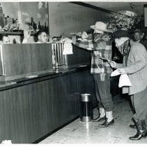 Image of Round-Up Days, 1951 - This is a photograph featuring cowboy robbers armed with six-shooters and masks holding up the Mt. Greenwood State Bank, 3052 W. 111th Street, to launch Oak Lawn's annual Round-Up, a three-day festival. The bandits, Ken Shoot (left) and James Sweeney (right), co-chairmen of the Oak Lawn Chamber of Commerce, hold cashier George Noonan at bay while their comrades rob the bank.
