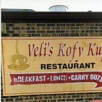 Image of Veli's Kofy Kup Sign - This is photograph featuring the sign from Veli's Kofy Kup which was formerly located at 5253 W. 95th Street until the early 2000s. The sign now resides on the back outside wall of B. J. McMahon's located at 5432 95th Street.