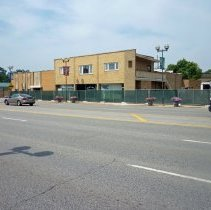Image of 95th and Raymond Redevelopment  - This is a photograph of a construction site on the northwest corner of 95th Street and Raymond Avenue. A construction fence surrounds the former village parking lot. This is the beginning of the construction of the Oak Lawn Bank and Trust to be located at 5300 west 95th Street. The first building on the left is Suburban Plastic Surgery located at 5346 95th Street, followed by the former Oak Lawn Senior Center located at 5330 W. 95th Street, Rutledge Printing Company located at 5316 W. 95th Street, the former Oak Lawn Chamber of Commerce located at 5314 W. 95th Street, and American Home Loans located at 5312 W. 95th Street. The buildings on the northwest corner of the block have since been demolished.