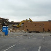 Image of 95th and Raymond Redevelopment  - This is a photograph of a construction site on the northwest corner of 95th Street and Raymond Avenue. This is the beginning of the construction of the Oak Lawn Bank and Trust to be located at 5300 west 95th Street. The former Oak Lawn Chamber of Commerce located at 5314 W. 95th Street, and American Home Loans located at 5312 W. 95th Street are shown being demolished.  Construction workers can be seen sitting down on equipment.