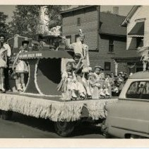 Image of Oak Lawn Round-Up Days - This is a photograph featuring the Oak Lawn Roller Rink float in the annual Round-Up parade. A number of individuals are seated on the float as it moves down 95th Street near Cook Avenue. Businesses such as McKay's Jewelry (5216 West 95th Street) and Reno's Sports and Hobbies (5210 West 95th Street) are visible in the background.