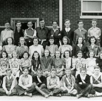 Image of Simmons School Class Photo - This is a photograph of students at the Ridgeland District 122 School (now known as Simmons Middle School). The students are unidentified. Wiley Simmons, seen in the left of the picture, and his wife Pearl, came to teach at the school for the 1925-1926 school year. The school was a modern two-room school, complete with electricity constructed in 1922 about a half-block west of the one-room frame building which originally stood on the northwest corner of Ridgeland Avenue and 95th Street. When the school was later expanded, it was named after Simmons who also served as the school district's first Superintendent.