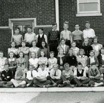 Image of Simmons School Class Photo - This is a photograph of students at the Ridgeland District 122 School (now known as Simmons Middle School). The students and the teacher are unidentified. Wiley Simmons and his wife, Pearl, came to teach at the school for the 1925-1926 school year. The school was a modern two-room school, complete with electricity constructed in 1922 about a half-block west of the one-room frame building which originally stood on the northwest corner of Ridgeland Avenue and 95th Street. When the school was later expanded, it was named after Wiley Simmons who also served as the school district's first Superintendent.
