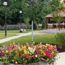 Image of Village Green and Gazebo - This is a photograph of the gazebo on the Village Green. Some of the park's paths, landscaping, and a flower pot planted with colorful flowers are also visible. Two men with small dogs are seen in the center of the picture.