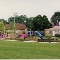 Image of Village Green Playground - This is a photograph of the playground equipment on the north side of the Village Green. The backs of residential homes along the south side of Oak Street can be seen in the background. The parking lot of the Village Safety Center located at 9446 S. Raymond Avenue is partially visible in the background.