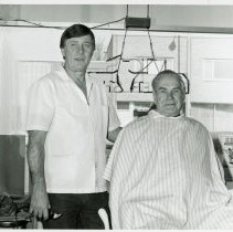 Image of Vic's Barber Shop - This is a photograph featuring Mr. Vic Sobol in his shop, Vic's Barber Shop, located at 5321 W. 95th Street. The customer in his chair is Ed Kasper. A pay phone is seen on the left. In the background, businesses located on the north side of 95th Street are visible including Rutledge Printing Company located at 5316 W. 95th Street and the office of accountant Joseph W. Francis at 5314 W. 95th Street.