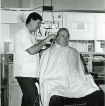 Image of Vic's Barber Shop - This is a photograph featuring Mr. Vic Sobol in his shop, Vic's Barber Shop, located at 5321 W. 95th Street. The customer in his chair is Ed Kasper. In the background, businesses located on the north side of 95th Street are visible including Rutledge Printing Company located at 5316 W. 95th Street and the office of accountant Joseph W. Francis at 5314 W. 95th Street. There appears to be snow on the ground.