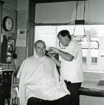 Image of Vic's Barber Shop - This is a photograph featuring Mr. Vic Sobol in his shop, Vic's Barber Shop, located at 5321 W. 95th Street. The customer in his chair is Ed Kasper. A pay phone is seen on the left. In the background, businesses located on the north side of 95th Street are visible including Rutledge Printing Company located at 5316 W. 95th Street and the office of accountant Joseph W. Francis at 5314 W. 95th Street. There appears to be snow on the ground.