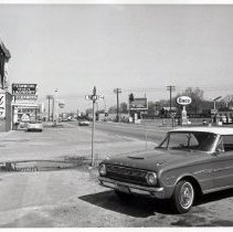 Image of 95th Street & Tulley Avenue, 1964 - This is a photograph of 95th Street looking east from the north side of the street at Tulley Avenue. A 1963 Ford Falcon Sprint convertible is parked in front of Steve's Coin Shop located at 5130 W. 95th Street. This building used to serve as the Oak Lawn Post office. In the background, Fernwood Smith Cleaners, located at 5114 W. 95th Street and a Shell station can be seen. An advertisement for TV Sales and Service is also visible on the side of a building located at 5100 W. 95th Street. The railroad gates and crossing are visible. On the south side of 95th Street, a cement truck can be seen turning into the Wm. Brandt & Son yard. A billboard for the I.N.R. Beatty Lumber Company is seen overhead. The Humble Oil & Refining Company Enco gas station located at 5103 W. 95th Street is seen to the left.