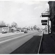 Image of 95th Street & Tulley Avenue, 1964 - This is a photograph of 95th Street looking east from the south side of the street at Tulley Avenue. Fernwood Smith Cleaners, located at 5114 W. 95th Street and a Shell station can be seen. An advertisement for TV Sales and Service is also visible on the side of a building located at 5100 W. 95th Street. The railroad gates and crossing are visible. Across the tracks, the white building with an open service door belongs to Ingerson Rambler located at 5000 W. 95th Street. On the south side of 95th Street, in the background, the Humble Oil & Refining Company Enco gas station located at 5103 W. 95th Street is visible. The building seen on the left is the Brandt building located at 5131 W. 95th Street. It housed Brandt's Tavern and Craig's Barber Shop, 5135 W. 95th Street, as well as several other businesses. A Nectar Beer and Liquors sign as well as a barber pole are seen outside the building.