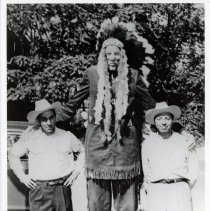 Image of Donald A. Koehler - This is a photograph of Donald A. (Bud) Koehler, believed to be the tallest man in America in 1952, dressed as an Indian and posing with two unidentified men. Koehler appeared in several Oak Lawn Round Up Day parades during the 1950s. Donald A. Koehler is one of 17 known people in medical history to reach a height of 8 feet or more. He was generally recognized as the tallest living man in the world from at least 1969 until his death in 1981.