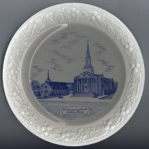 Image of First Congregational Church Commemorative Plate - This item is a commemorative plate created for the First Congregational Church, now known as Pilgrim Faith United Church of Christ, located at 9411 South 51st Avenue. It is white and blue in color and features an image of the church structure on the front. The back has a short history.