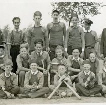 Image of Simmons School - This is a photograph of a group of students, possibly a baseball team, from District 122 Simmons School. Several of the people in the picture are wearing shirts emblazoned with a shield and the letters S/S. It is believed that this stands for Simmons School. Two students wear graduations ribbons. Simmons School, originally known as the District 122 School, was named for Wiley Simmons in 1942. Wiley and his wife Pearl, came to teach at the school in 1925 and were the only teachers at the school until the early 1930s. When a second school had to be built in the 1940s, the 8th grade students submitted two names to the school board. Simmons name was picked for the original school and the other new school was eventually named Harnew School. Wiley Simmons, the man for whom the school was named, is pictured on the far right. In September of 1942, Simmons was named Superintendent of District 122 as well as Principal, making him the first Superintendent of the District. The rest of the people in the picture are unidentified.