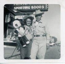 "Image of Round-Up Days, 1953 - This is a photograph of the 1953 Oak Lawn Round-Up Days celebration. There are two individuals present wearing Western themed attire and labeled as ""Dee and George"". Behrend's Hardware, located at 5300 West 95th Street, is directly behind them while the Sinclair Service Station sign is visible in the background."