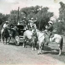 Image of Round-Up Days, 1952 - This is a photograph of the 1953 Oak Lawn Round-Up Days celebration. It features a stagecoach being held up by two gunmen. A female passenger is in the coach with her hands up. The driver hands over a bag of loot as the other driver looks on with his hands up.
