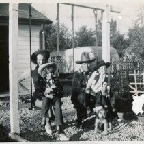 Image of Round-Up Days, 1951 - This is a photograph of a family dressed for the 1951 Oak Lawn Round-Up Days celebration. The family is seated on a swing set in what appears to be the back yard of a residence. Grace Rainville and Edith Rainville (seated) are on the left while Jerry Sullivan and Mary Ann (Sullivan) Bult are on the right. A garage and a camper can be seen in the background. Held from 1949-1958, the Round-Up was a western themed celebration that included a parade, rides, and other events.