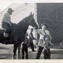 Image of Round-Up Days, 1951 - This is a photograph of an unidentified rider on horseback stopping to let a woman, Grace Rainville, and her two children, Edith and Pete Rainville, pet the horse during the 1951 Oak Lawn Round-Up Days celebration. All are dressed in western wear. A man pushing what is believed to be a baby stroller is partially visible behind them. Held from 1949-1958, the Round-Up was a western themed celebration that included a parade, rides, and other events.