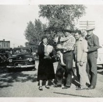 Image of Round-Up Days, 1951 - This is a photograph of several unidentified people posing for a picture behind the Brandt building during the 1951 Oak Lawn Round-Up Days celebration. Cars can be seen parked behind the Brandt building and another car is moving toward the group from behind. A rider on horseback is also visible in the background. A railroad boxcar is seen on the right. Held from 1949-1958, the Round-Up was a western themed celebration that included a parade, rides, and other events.