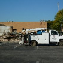 Image of 95th and Raymond Redevelopment  - This is a photograph of a construction site on the northwest corner of 95th Street and Raymond Avenue. This is the beginning of the construction of the Oak Lawn Bank and Trust to be located at 5300 west 95th Street. The former Oak Lawn Chamber of Commerce located at 5314 W. 95th Street, and American Home Loans located at 5312 W. 95th Street are shown being demolished. A truck from American Demolition is parked in the foreground.