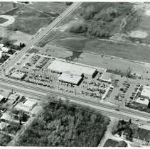 Image of Aerial Photograph of 95th Street & Oak Park Avenue - This is an aerial photograph of 95th Street and Oak Park Avenue looking southeast to northwest. 95th Street is visible in the bottom of the picture running diagonally from left (west) to right (east). Oak Park Avenue is seen in the left of the photo running from bottom (south) to top (north). Businesses from l-r include, Bruce's Champion Service Station located at 6800 W. 95th Street (northwest corner of 95th Street & Oak Park Avenue), Jack Rutledge Buick, located at 6750 W. 95th Street, and Chicago Health and Racquet Club, located at 6700 W. 95th Street. In the upper portion of the picture, Oak Lawn baseball field are visible on both the west and east sides of Oak Park Avenue. The empty land in the center of the photograph will eventually be the site of the Oak Lawn Park District Pavilion. Two fire trucks can be seen in the Park District parking lot behind the car dealership with a large wet area between them. The Oak Park Amoco station, located at 6757 W. 95th Street can be seen in the very left bottom of the photo on the southeast corner of the intersection of 95th Street and Oak Park Avenue.