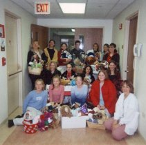 Image of Simmons Junior High Service Project - This is a photograph of a contingent of Simmons Junior High School (now known as Simmons Middle School) students delivering baskets of stuffed animals at what appears to be a hospital as part of a service project. The individuals in the photograph are unidentified.