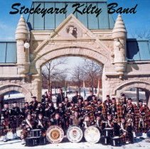 Image of Stockyard Kilty Band Postcard - This item is a postcard of the Stockyard Kilty Band. The members of the band are posing before the Union Stockyard Gate located near Exchange Avenue and Peoria Street in Chicago. Founded in 1921, the organization had a P.O. Box in Oak Lawn.