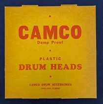 Image of Camco Plastic Drum Head  - This item is a plastic drum head produced by the Camco Drum Company. The business had two different Oak Lawn addresses at 9221 South Kilpatrick Avenue and 9536 South Tulley Avenue. The item is white in color and came packaged in a yellow box.