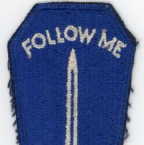 """Image of U.S. Army Infantry School Patch  - This item is a patch from the U.S. Army Infantry School used during World War II. It is blue in color and features an image of a sword with the words """"Follow Me"""" above it."""