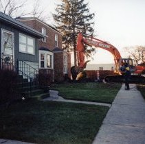 Image of 9427 South Tulley Avenue - This is a photograph featuring the start of the demolition of the home located at 9427 South Tulley Avenue. It is being demolished to make way for the 51st Avenue Station development which includes stores and a condominium building. An excavator is seen beginning the demolition at the front of the home and the stairs have already been removed. The home seen in the foreground on the left is located at 9423 South Tulley Avenue. The white building partially visible in the background is believed to be a temporary sales office for the condominium building that was eventually built on the site.