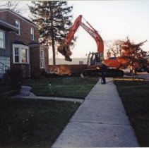 Image of 9427 South Tulley Avenue - This is a photograph featuring the start of the demolition of the home located at 9427 South Tulley Avenue. A man in a hard hat looks on appears to be holding a firehose. It is being demolished to make way for the 51st Avenue Station development which includes stores and a condominium building. An excavator is seen beginning the demolition at the front of the home and the stairs have already been removed. The home seen in the foreground on the left is located at 9423 South Tulley Avenue. In the background on the right, Krauss Gaslight Lounge, located at 5130 W. 95th Street is partially visible. The white building partially visible in the background is believed to be a temporary sales office for the condominium building that was eventually built on the site.