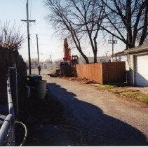 Image of 9427 South Tulley Avenue - This is a photograph featuring a view of an excavator demolishing the fence behind the home located at 9427 South Tulley. The home on the site has already been torn down and was demolished to make way for the 51st Avenue Station development which includes stores and a condominium building. The white building partially visible in the background is believed to be a temporary sales office for the condominium building that was eventually built on the site.