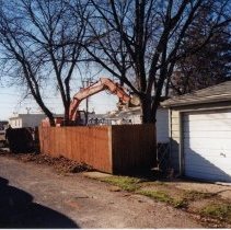 Image of 9427 South Tulley Avenue - This is a photograph featuring a view of an excavator demolishing the garage behind the home located at 9427 South Tulley. The home on the site has already been torn down and was demolished to make way for the 51st Avenue Station development which includes stores and a condominium building. The white building partially visible in the background is believed to be a temporary sales office for the condominium building that was eventually built on the site.
