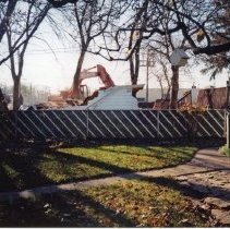 Image of 9427 South Tulley Avenue - This is a photograph featuring an excavator demolishing the garage behind the home located at 9427 South Tulley. The home on the site has already been torn down and was demolished to make way for the 51st Avenue Station development which includes stores and a condominium building. The photograph was taken from the back yard of the home next door located at 9423 S. Tulley. The white building partially visible in the background is believed to be a temporary sales office for the condominium building that was eventually built on the site. Hollywood Video can be seen on the far right.