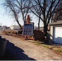 Image of 9427 South Tulley Avenue - This is a photograph featuring a view from the alley behind the home located at 9427 South Tulley. An excavator is demolishing the fence as another worker looks on. The home and the garage on the site have already been torn down. The home was demolished to make way for the 51st Avenue Station development which includes stores and a condominium building. The white building partially visible in the left background is believed to be a temporary sales office for the condominium building that was eventually built on the site.
