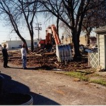 Image of 9427 South Tulley Avenue - This is a photograph featuring a view from the alley behind the home located at 9427 South Tulley. An excavator is gathering debris from the demolished garage and fence as two other workers looks on. The home and garage on the site was demolished to make way for the 51st Avenue Station development which includes stores and a condominium building. In the background on the right, Krauss Gaslight Lounge, located at 5130 W. 95th Street is partially visible. The white building partially visible in the background is believed to be a temporary sales office for the condominium building that was eventually built on the site.