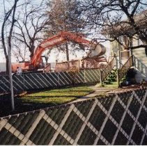 Image of 9427 South Tulley Avenue - This is a photograph featuring a view from behind the home located at 9423 South Tulley Avenue. An excavator is demolishing the back porch deck of 9427 South Tulley. The home on the site was demolished to make way for the 51st Avenue Station development which includes stores and a condominium building. In the background on the right, Krauss Gaslight Lounge, located at 5130 W. 95th Street is partially visible. The white building partially visible in the left background is believed to be a temporary sales office for the condominium building that was eventually built on the site.