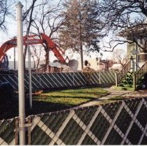 Image of 9427 South Tulley Avenue - This is a photograph featuring a view from behind the home located at 9423 South Tulley Avenue. An excavator is demolishing the back porch deck of 9427 South Tulley. The home on the site was demolished to make way for the 51st Avenue Station development which includes stores and a condominium building. In the background on the right, Krauss Gaslight Lounge, located at 5130 W. 95th Street is partially visible. Hollywood Video can also be seen in the distance. The white building partially visible in the left background is believed to be a temporary sales office for the condominium building that was eventually built on the site.