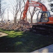 Image of 9427 South Tulley Avenue - This is a photograph featuring an excavator loading debris from a demolished home located at 9427 South Tulley Avenue into a dump. The dump truck is partially visible behind the machine on the right. The home on the site was demolished to make way for the 51st Avenue Station development which includes stores and a condominium building. The home partially visible on the left is located at 9423 S. Tulley.