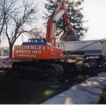 Image of 9427 South Tulley Avenue - This is a photograph featuring a view of an excavator loading debris from a demolished home located at 9427 South Tulley Avenue into a dump truck. The home on the site was demolished to make way for the 51st Avenue Station development which includes stores and a condominium building. The white building partially visible in the background between the dump truck and its tractor is believed to be a temporary sales office for the condominium building that was eventually built on the site.