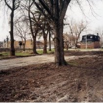 Image of 9427 South Tulley Avenue - This is a photograph featuring a view of the former site of a home located at 9427 South Tulley Avenue. This view is looking from the alley east of Tulley Avenue to the southwest. The home was demolished on November 19, 2003 to make way for the 51st Avenue Station development which includes stores and a condominium building. In the background on the right, Krauss Gaslight Lounge, located at 5130 W. 95th Street, and homes along the west side of Tulley Avenue are visible. The white building partially visible in the very left of the photography is believed to be a temporary sales office for the condominium building that was eventually built on the site.