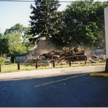 Image of 9429 South Tulley Avenue - This is a photograph featuring a view of a bulldozer demolishing the Deplaris home located at 9429 S. Tulley. The home was demolished in 1999 to provide parking for businesses along the north side of 95th Street. The building on the right is the Fernwood Smith Cleaners building located at 5114 W.95th Street, on the northeast corner of Tulley Avenue and 95th Street. The same building also housed the A & B Oak Lawn Currency Exchange which was located at 5112 West 95th Street, Millie's Ice Cream and Coffee Shoppe which was located at 5108 West 95th Street. This entire building was eventually demolished in 2001 to make way for the 51st Avenue Station development which includes stores and a condominium building.