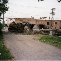 Image of 9429 South Tulley Avenue - This is a photograph featuring a bulldozer demolishing the Deplaris home located at 9429 S. Tulley. The home was demolished in 1999 to provide parking for businesses along the north side of 95th Street. The building in the background housed A & B Oak Lawn Currency Exchange which was located at 5112 West 95th Street, Millie's Ice Cream and Coffee Shoppe which was located at 5108 West 95th Street, and the Fernwood Smith Cleaners located at 5114 W.95th Street, on the northeast corner of Tulley Avenue and 95th Street. This entire building was eventually demolished in 2001 to make way for the 51st Avenue Station development which includes stores and a condominium building. In the background on the right, the east facade of Krauss Gaslight Lounge located at 5130 W. 95th Street is visible.