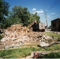 Image of 9429 South Tulley Avenue - This is a photograph featuring a bulldozer loading debris from the demolished Deplaris home located at 9429 S. Tulley into a dump truck. The home was demolished in 1999 to provide parking for businesses along the north side of 95th Street. In the background in the very left of the photograph, the side entrance of Pilgrim Faith United Church of Christ located at 9411 S. 51st Avenue is visible. The building seen on the right housed A & B Oak Lawn Currency Exchange which was located at 5112 West 95th Street, Millie's Ice Cream and Coffee Shoppe which was located at 5108 West 95th Street, and the Fernwood Smith Cleaners located at 5114 W.95th Street, on the northeast corner of Tulley Avenue and 95th Street. This entire building was eventually demolished in 2001 to make way for the 51st Avenue Station development which includes stores and a condominium building.