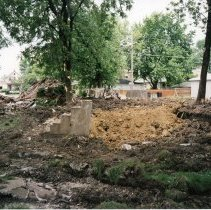 Image of 9444 South 51st Avenue - This is a photograph featuring a view of the site of a home located at 9444 S. 51st Avenue. The home was demolished in 1999 to provide parking for businesses along the north side of 95th Street. In the left background, trucks in the parking lot of a business on 95th Street and a home located on the west side of Tulley Avenue are visible. On the left, the backs of homes across the alley on the east side of Tulley Avenue can be seen.