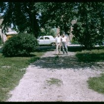 Image of 9126 South 54th Avenue - This is a photograph featuring a view of Charles Bakutis and his son, Chuck standing in the driveway of the home located at 9126 S. 54th Avenue. The view is looking down the driveway from west to east. The home, seen in the left of the picture, was purchased by Viola and Charles Bakutis in 1953. Today the home is know as the Chapman House (Harker Farm House), a historical landmark that was built in 1924. The home was built on vertical poles and had no foundation. There was a cellar in the rear of the house that contained a coal burning furnace and coal bin. Bakutis later put in a foundation and enlarged the cellar. A car of the era is seen parked on the street and homes on the east side of 54th Avenue are partially visible.