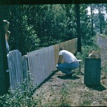 Image of 9126 South 54th Avenue - This is a photograph featuring a view of the alley behind the home located at 9126 S. 54th Avenue. Chuck Bakutis is painting the fence. Another man, possibly his father, Charles Bakutis, looks on from behind the gate. The home was purchased by Viola and Charles Bakutis in 1953. Today it is known as the Chapman House (Harker Farm House), a historical landmark that was built in 1924. The home was built on vertical poles and had no foundation. There was a cellar in the rear of the house that contained a coal burning furnace and coal bin. Bakutis later put in a foundation and enlarged the cellar.