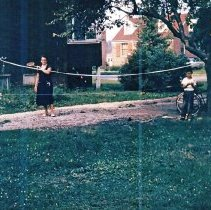 Image of 9126 South 54th Avenue - This is a photograph featuring a view of Irene Steffen and her children Robert Steffen and Patricia Steffen, playing badminton in the side yard of the home located at 9126 S. 54th Avenue. This view is looking from southwest to northeast and the south facade and front porch of the home are seen on the left. The home was purchased by Viola and Charles Bakutis in 1953. Today it is known as the Chapman House (Harker Farm House), a historical landmark that was built in 1924. The home was built on vertical poles and had no foundation. There was a cellar in the rear of the house that contained a coal burning furnace and coal bin. Bakutis later put in a foundation and enlarged the cellar.