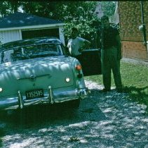 Image of 9126 South 54th Avenue - This is a photograph featuring a car in the driveway of the home located at 9126 S. 54th Avenue. The man behind the wheel of the car is believed to be Charles Bakutis, the homeowner. The two boys about to enter the car are unidentified. The south facade of the home is seen on the right. The home was purchased by Viola and Charles Bakutis in 1953. Today it is known as the Chapman House (Harker Farm House), a historical landmark that was built in 1924. The home was built on vertical poles and had no foundation. There was a cellar in the rear of the house that contained a coal burning furnace and coal bin. Bakutis later put in a foundation and enlarged the cellar.